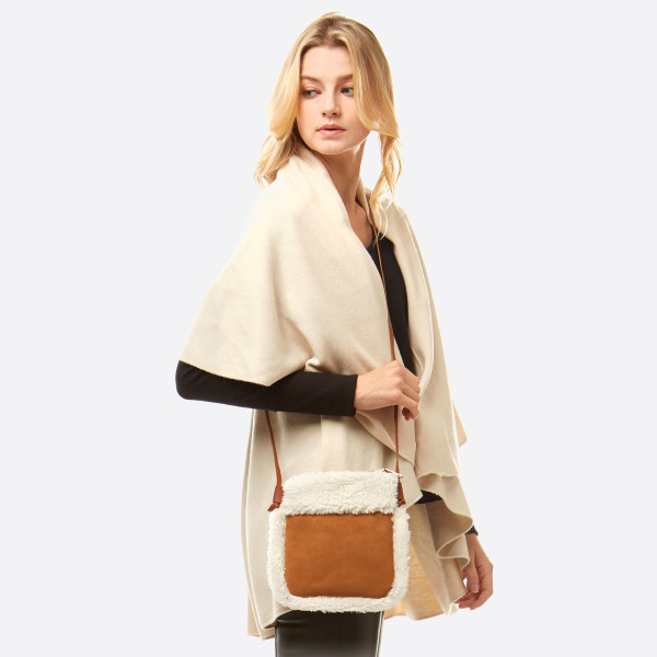 """Faux suede sherpa fleece lined crossbody bag featuring:  - No inside pockets - Zipper closure  - Approximately 6"""" W x 8"""" T - 100% Polyester"""