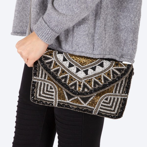 """High quality black, gold and white geometric seed beaded handbag.  - Fold over snap button closure - One inside open pocket - Inside lining 100% Cotton - Approximately 10.5"""" W x 6"""" T - Strap approximately 52"""" L - Approximately 62"""" L overall - 40% Seed beads, 40% Cotton Canvas, 20% Metal"""