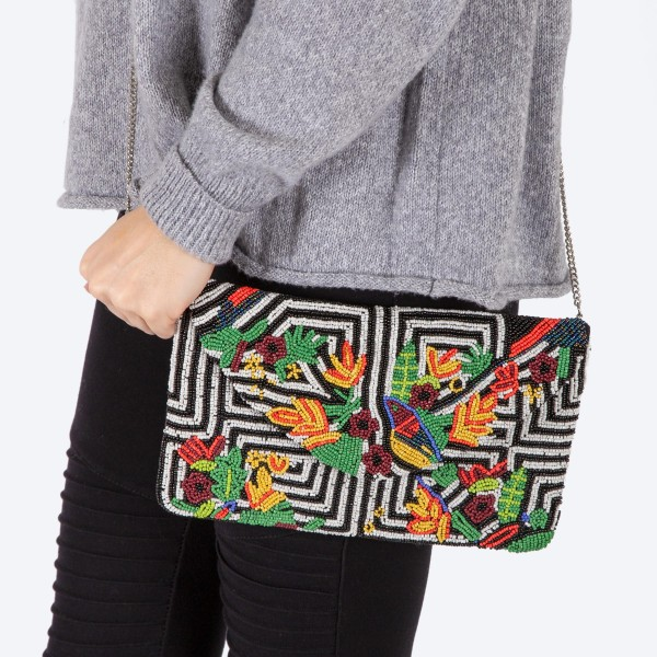 """High quality black and white stripe tropical floral print handbag.  - Fold over snap button closure - One inside open pocket - Inside lining 100% Cotton - Approximately 10.5"""" W x 6"""" T - Strap approximately 52"""" L - Approximately 62"""" L overall - 40% Seed beads, 40% Cotton Canvas, 20% Metal"""