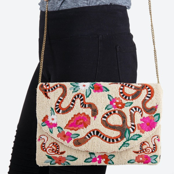 """High quality seed beaded designer inspired floral embroidered crossbody clutch.  - Open lined inside - 1 open functional pocket - Fold over flap button closure - Approximately 10"""" W x 6"""" T - Strap hangs 21"""" L - 100% Cotton"""