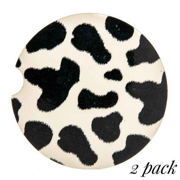 """Cow printed car coaster set.   - Pack Breakdown: 2pcs / pack - Approximately 2"""" in diameter - Finger slot for easy removal - Condensation absorbing cork"""