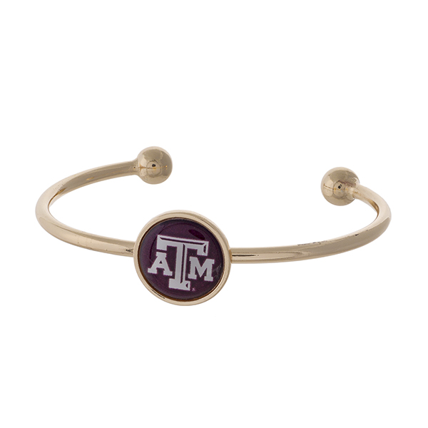 Officially licensed, gold tone cuff bracelet with the Texas A&M University logo.