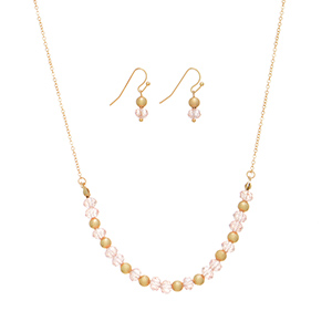 "Gold tone necklace set featuring pink beads and gold tone metal beads. Approximately 16"" in length."