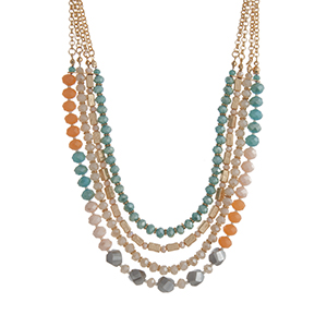"""Gold tone layering necklace displaying strands of turquoise, peach, and ivory glass beads. Approximately 18"""" in length."""