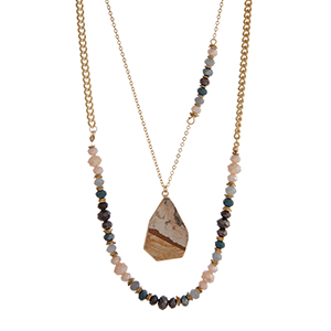 "Gold tone layering necklace displaying ivory, teal, and black glass beads with a brown natural stone pendant. Approximately 21"" in length."