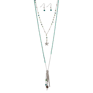 "Silver tone layering necklace set displaying turquoise beads with a starfish and coral reef charms, hanging chains, and two bars. Approximately 31"" in length."