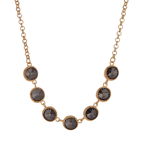 "Matte gold tone necklace displaying round black diamond rhinestones. Approximately 17"" in length."