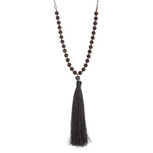 "Burnished gold tone necklace with brown beads and a 5 1/4"" gray fabric tassel. Approximately 30"" in length."