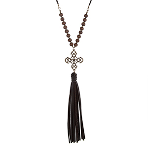 "Brown faux leather necklace displaying wood beads, a burnished gold tone cross charm, and a 5 1/2"" tassel. Approximately 29"" in length."