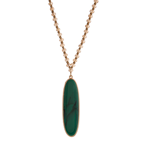 "Champagne and gold tone beaded necklace with a green oval shape pendant. Approximately 30"" in length."