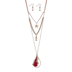 "Gold tone pink beaded layering necklace set displaying a chevron pattern with a starfish a fish charm and an open teardrop shape with a red fabric tassel and sea life charms. Approximately 31"" in length."
