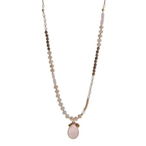 "Gold tone necklace with peach beads and a rose pink teardrop pendant. Approximately 32"" in length."