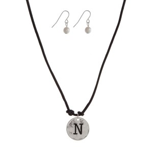 "Black cord necklace with a silver tone pendant stamped with the letter ""N"" and a pearl closure. Approximately 18"" in length."