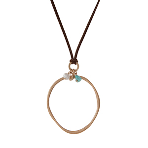 """Brown cord necklace displaying an open circle pendant and turquoise and pearl beads. Approximately 32"""" in length."""