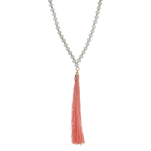 """Light blue beaded necklace with a peach fabric tassel. Approximately 36"""" in length."""
