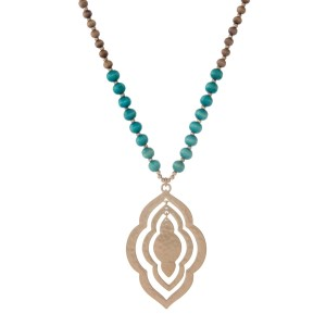 """Brown wooden beaded necklace with turquoise beads displaying a quatrefoil shape pendant. Approximately 32"""" in length."""