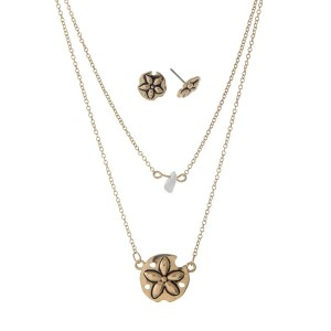 "Dainty double layer gold tone necklace set with a white chip stone and a sand dollar pendant. Approximately 18"" in length."