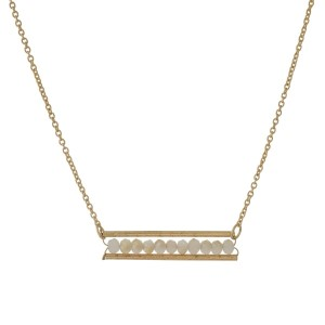 """Dainty gold tone necklace with a bar pendant accented with ivory beads. Approximately 16"""" in length."""