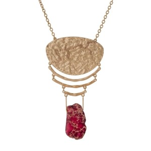 "Gold tone necklace with a hammered pendant and a red natural stone. Approximately 32"" in length."