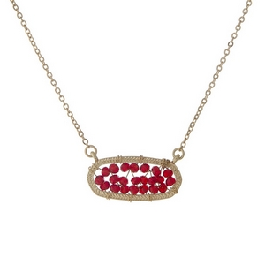 "Gold tone necklace with a red beaded oval pendant. Approximately 16"" in length."