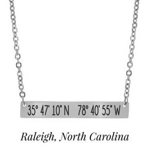 "Silver tone necklace with a bar pendant stamped with the coordinates of Raleigh, North Carolina. Approximately 18"" in length."