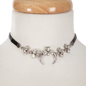 """Black faux leather choker with a silver tone crescent focal, accented with clear rhinestones. Approximately 12"""" in length."""