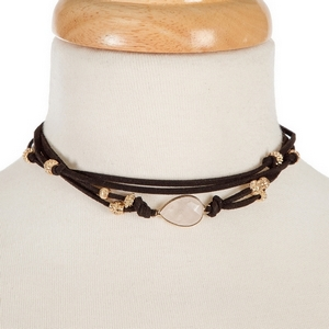 """Black faux suede choker with gold tone accents and a clear teardrop stone focal. Approximately 12"""" in length."""