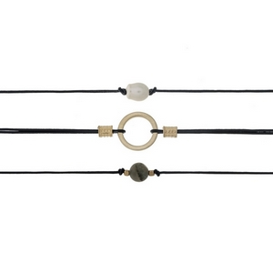 "Three piece black cord choker set with freshwater pearl bead and a gray natural stone bead. Approximately 12"" in length."