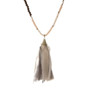 """Champagne, peach and brown beaded necklace with a gray and ivory fabric tassel. Approximately 32"""" in length."""
