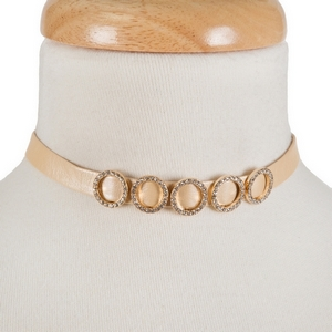 "Peach, faux leather choker with gold tone circles and clear rhinestone accents. Approximately 12"" in length."