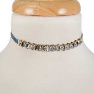 "Denim choker with clear rhinestones and gold tone accents. Approximately 12"" in length."