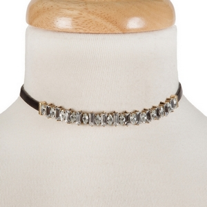 "Black faux leather choker with clear rhinestones and gold tone accents. Approximately 12"" in length."