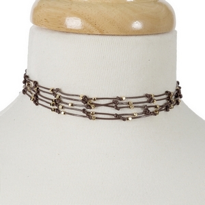 "Brown waxed cord choker with gold tone accents and a button closure. Approximately 12"" in length."