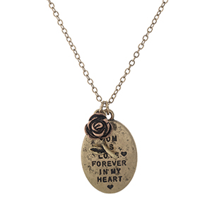 "Burnished gold tone necklace with a pendant stamped with "" A mom is love forever in my heart"" and accented with a flower charm. Approximately 16"" in length."