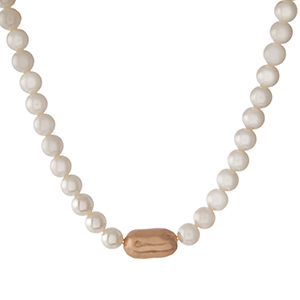 "Cream pearl beaded necklace with a hammered gold tone accent bead. Approximately 16"" in length."
