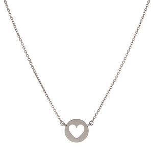 "Dainty silver tone necklace with a circle pendant displaying the cutout of a heart. Approximately 16"" in length."