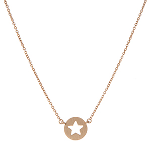 "Dainty gold tone necklace with a circle pendant displaying the cutout of a star. Approximately 16"" in length."