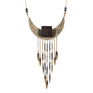 "Ivory cord necklace with a tribal pendant displaying varnished beads and metal fringe. Adjustable up to 32"" in length."