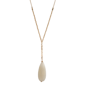 "Gold tone necklace with topaz faceted beads and an ivory natural stone pendant. Approximately 30"" in length."