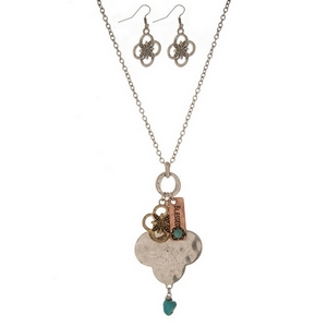 "Silver tone necklace set with a tri-tone flower pendant, stamped with ""Blessed"" and matching fishhook earrings. Approximately 27"" in length."