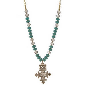 """Gold tone necklace with turquoise natural stone beads and an Ethiopian cross pendant. Approximately 16"""" in length. Handmade in the USA."""