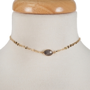 "Dainty gold tone choker with a gray stone focal. Approximately 12"" in length."