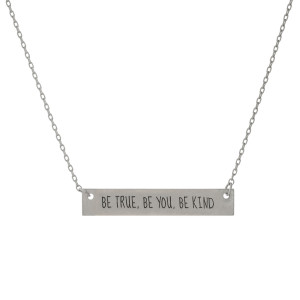 "Matte silver tone bar necklace stamped with ""Be True, Be You, Be Kind."" Approximately 14"" in length."