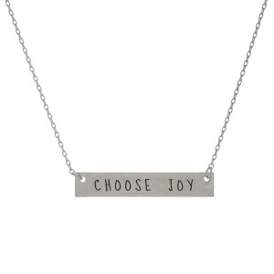 "Matte silver tone bar necklace stamped with ""Choose Joy."" Approximately 14"" in length."
