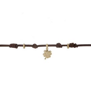 """Brown faux suede choker with a gold tone four leaf clover pendant. Approximately 12"""" in length."""