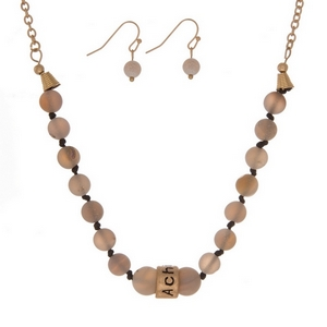"Matte gray, natural stone beaded necklace with a gold tone bead stamped with ""Achieve"" and matching fishhook earrings."