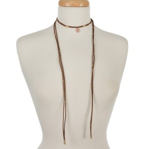 "Brown faux suede wrap necklace with gold tone accents and a peach stone. Approximately 60"" in length."