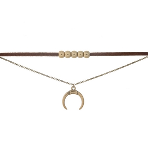 """Brown faux suede choker featuring a gold tone with a crescent pendant. Approximately 12"""" and 13"""" in length."""