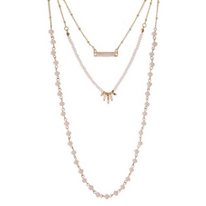 "Gold tone, three layer necklace with pink beads and a faux druzy stone pendant. Approximately 14"" to 18"" in length."