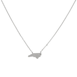 "Dainty silver tone necklace featuring a brushed North Carolina shaped pendant. Pendant approximately 7mm in length. Length adjusts from 16""-18""."